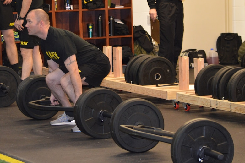 Soldiers in black shirts conducting physical training for the Army Combat Fitness Test. Soldier is conducting the Strength Dead Lift standing inside of power bar with black weights