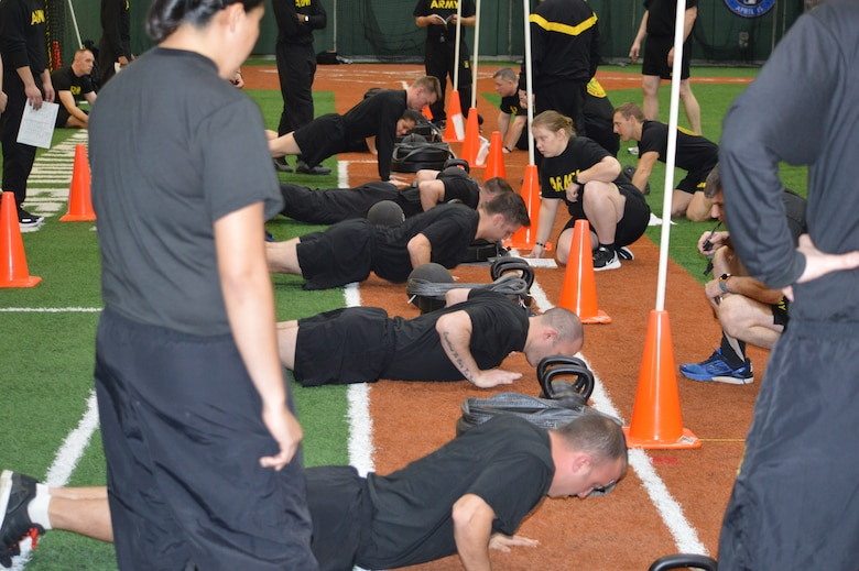 Soldiers in black shirts conducting physical training for the Army Combat Fitness Test. Soldiers conducting the Hand Release Push Up. Indoor stadium with orange and green turf