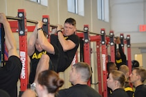 Soldiers in black shirts conducting physical training for the Army Combat Fitness Test. Pull Up bars are black with red beams with several Soldiers waiting in line for their turn.