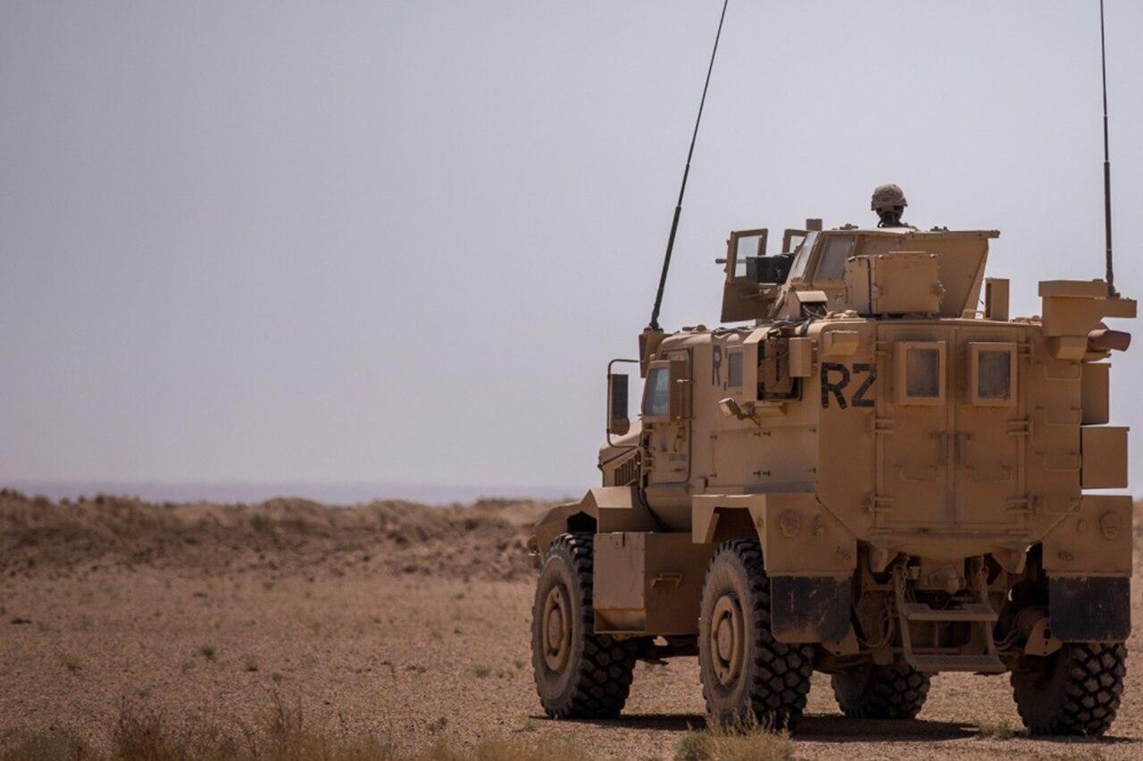 Military vehicle moves through desert.