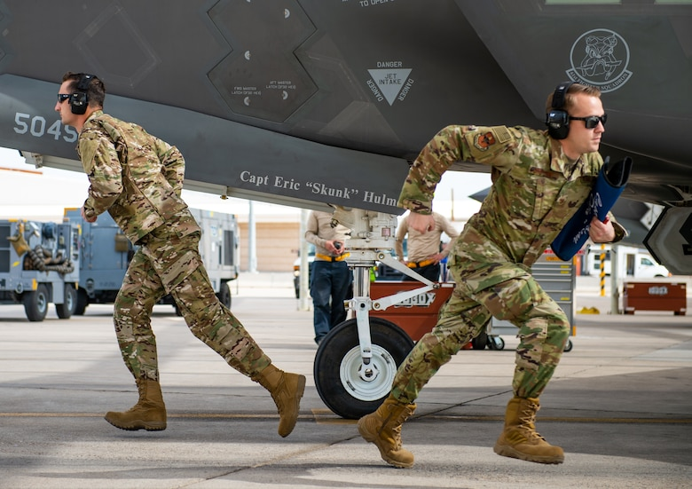 Staff Sgt. Paul Ogletree, F-35A Lighting II Demonstration Team dedicated crew chief, (left) and Tech. Sgt. Michael Couture, F-35 Demo Team lead (right) sprint to their positions during a ground performance Jan. 31, 2019, at Luke Air Force Base, Ariz. The team's newly developed ground performance features sharp, fast paced movements which highlight the pride and professionalism of the team and U.S Air Force. (U.S. Air Force photo by Senior Airman Alexander Cook)