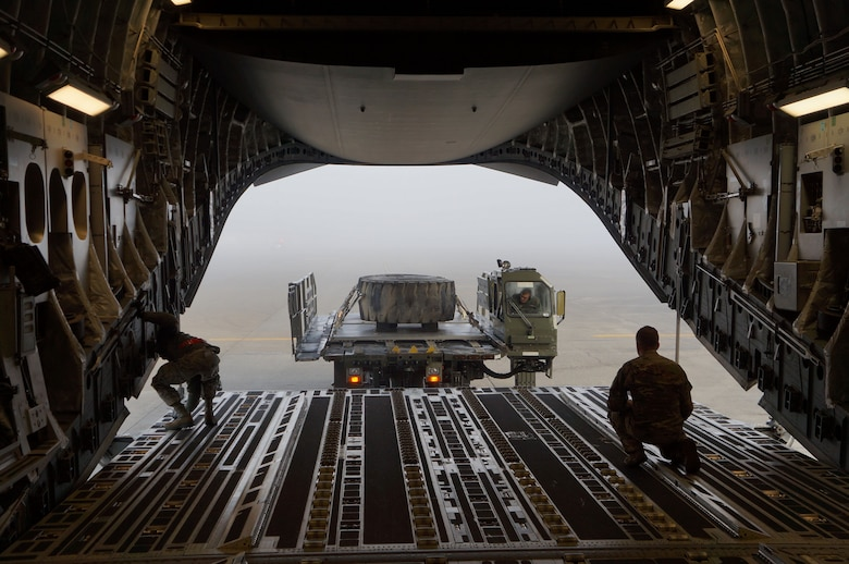 Staff Sgt. Zack Epperson, 313th Airlift Squadron loadmaster, and members of the 62nd Aerial Port Squadron work to load cargo for a combat offload simulation on a C-17 Globemaster III on McChord Field, Wash. (Courtesy photo)