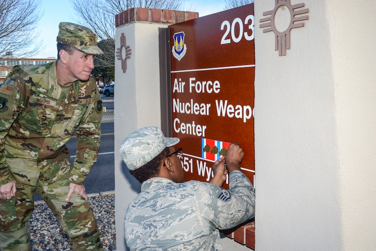 Air Force Nuclear Weapons Center Commander Maj. Gen. Shaun Morris and AFNWC's Staff Sgt. Mychavia Harris,  the center's most junior member in 2016, prepare to place a fourth oak leaf cluster on the center's sign on Wyoming Blvd. here Feb. 1, 2019. The oak leaf cluster was the center's fifth organizational excellence award since its inception in March of 2006. (U.S. Air Force photo by Jim Fisher)