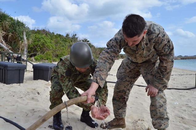 海兵隊員が陸自隊員に浄化水を見せています。