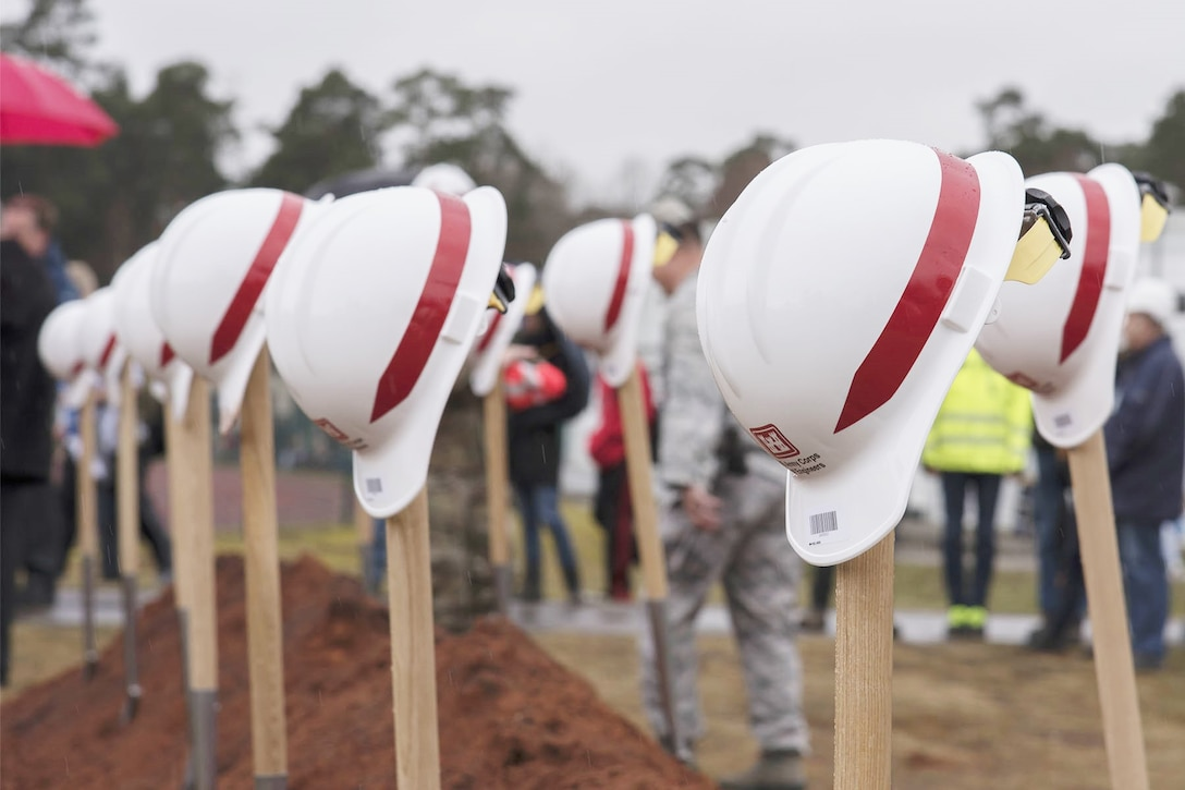 Hard hats balance on top of shovels sticking out of the ground.
