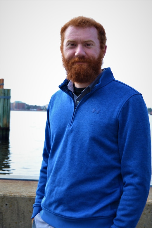man with blue sweater poses in front of water