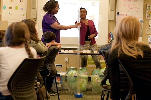 PETERSON AIR FORCE BASE, Colo. – Carol Rieping and Fola Davidson, 21st Force Support Squadron STARBASE instructors, demonstrate a project launch experiment, Jan. 31, 2019 at Peterson Air Force Base, Colorado. STARBASE Peterson is a school program that offers free enrichment programs that focus on teaching kids science technology engineering and math skills. (U.S. Air Force photo by Camer-on Hunt)