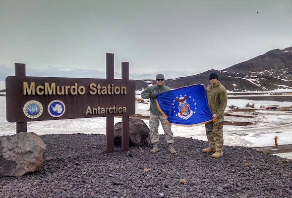 Chief Master Sgt. Troy Erlandson, 114th Fighter Wing occupational safety manager, holds the South Dakota flag with another Airman during his trip to McMurdo Station, Antarctica where he worked directly for Joint Force Antarctica to support the Antarctic research mission.