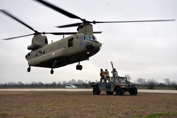 A Texas Army National Guard CH-47 Chinook approaches a Humvee as the ground crew prepares to hook connect the vehicle for airlifting during Operation Dust Storm at Martindale Army Air Field, Texas Feb. 1, 2019.