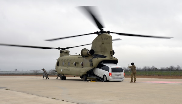 An Army National Guardsman guides a simulated ambulance out of a CH-47 Chinook during Operation Dust Storm Feb. 1, 2019 at Martindale Army Air Field, Texas.