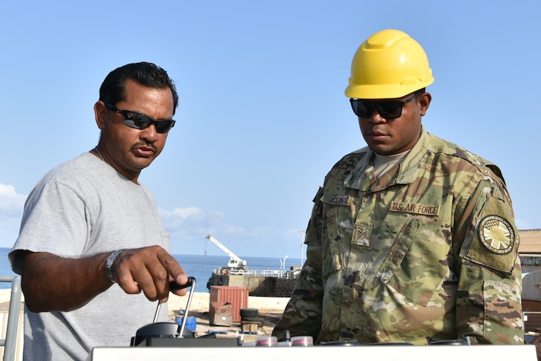 Tech. Sgt. Johntavion Jackson, 45th Civil Engineering Squadron contracting officer, looks over barge operating controls with an Ascension Island contractor, January 17, 2019 at Ascension Island Auxiliary Airfield. When Ascension receives supplies by ship, they can use barges to deliver supplies to the island. (U.S. Air Force photo by Airman 1st Class Dalton Williams)