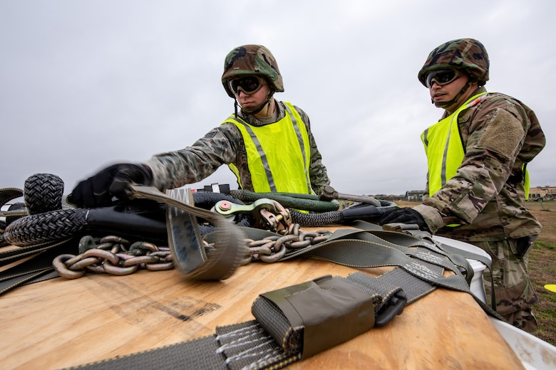 Senior Airman Timothy Watson, left, and Staff Sgt. Jose Frias, aerial transportation technicians, 26th Aerial Port Squadron, prepare to secure a 2,000-pound piece of cargo to a UH-60 Black Hawk helicopter flown by Soldiers from the Texas Army National Guard, Company C, 2-149 Aviation Regiment, during a sling load training event on Feb. 1, 2019, at Martindale Army Airfield, San Antonio, TX.