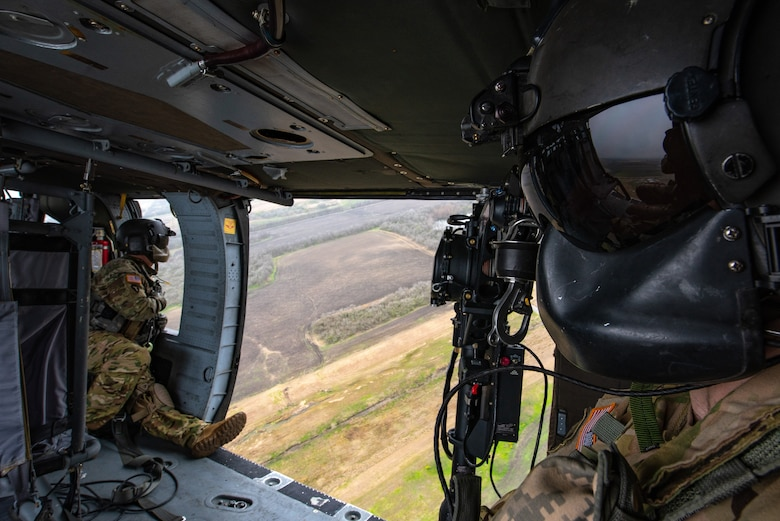 Sergeant First Class Dion Cortez, left, and Staff Sergeant Charles Jackson look out the doors of a UH-60 Black Hawk helicopter during a sling load training event at Martindale Army Airfield, San Antonio, TX, Feb. 1, 2019.