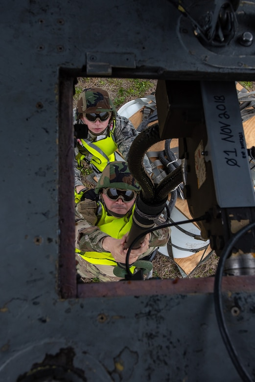 Staff Sgt. Jose Frias, aerial transportation technician, 26th Aerial Port Squadron, secures a 2,000-pound piece of cargo to a UH-60 Black Hawk helicopter flown by Soldiers from the Texas Army National Guard, Company C, 2-149 Aviation Regiment, during a sling load training event on Feb. 1, 2019, at Martindale Army Airfield, San Antonio, Texas.