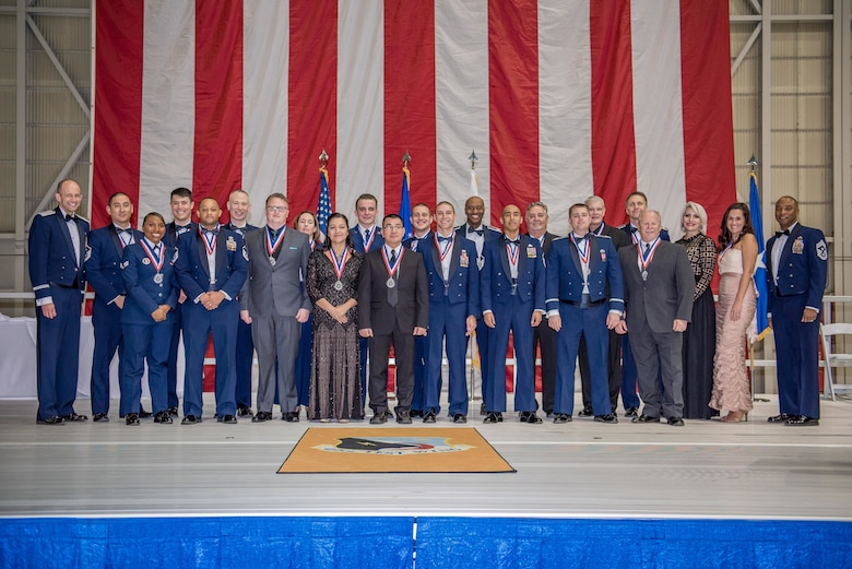 Brig. Gen. E. John Teichert (left), the 412th Test Wing commanding general and Command Chief Master Sergeant Roosevelt Jones, pose for a picture with the 2018 annual award winners during an awards banquet at Hangar 1600 on Edwards Air Force Base, California, Feb. 1.
