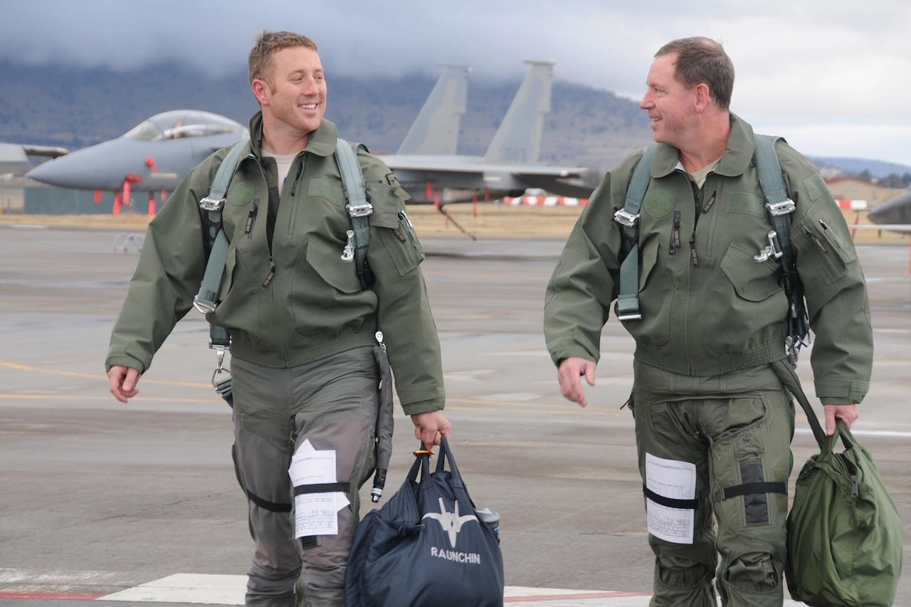 Two men walk on flight line