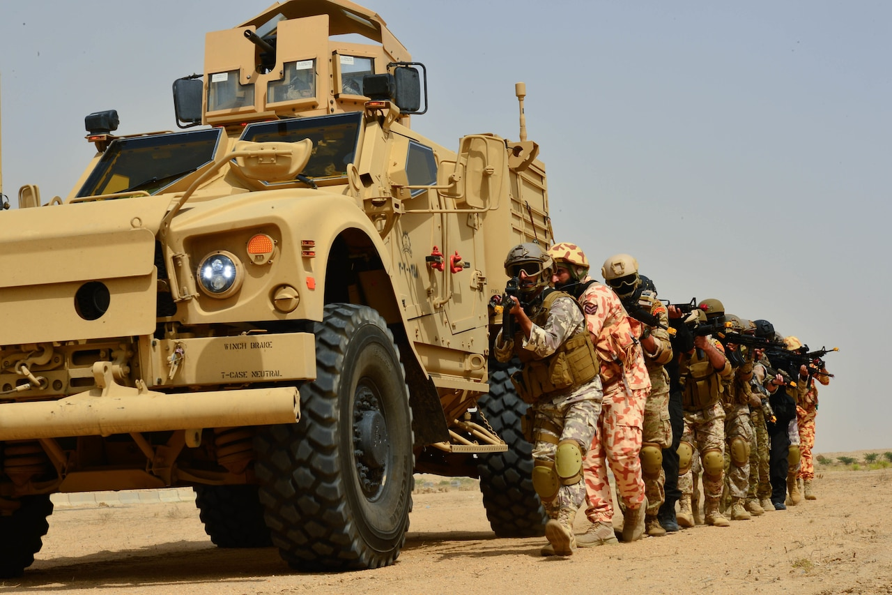 Troops with guns move forward next to truck