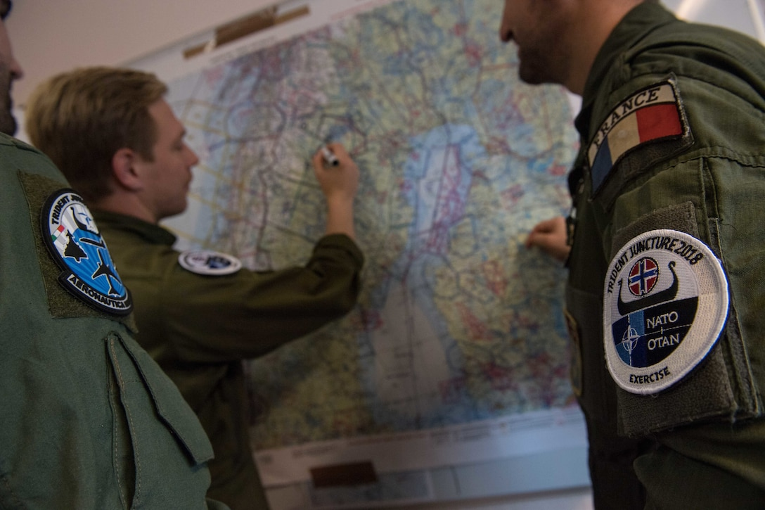 Three men in flight suits plan a flight on a wall map.