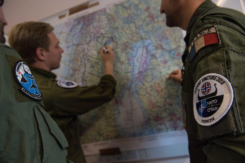 Three men in flight suits plan a flight on a wall map.
