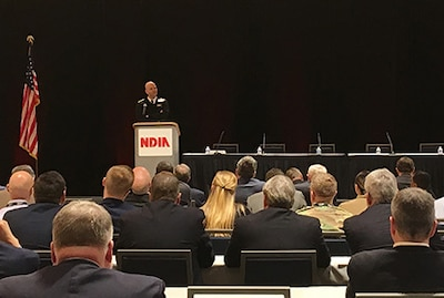 Navy Rear Adm. stands on stage behind a podium speaking to a crowded room