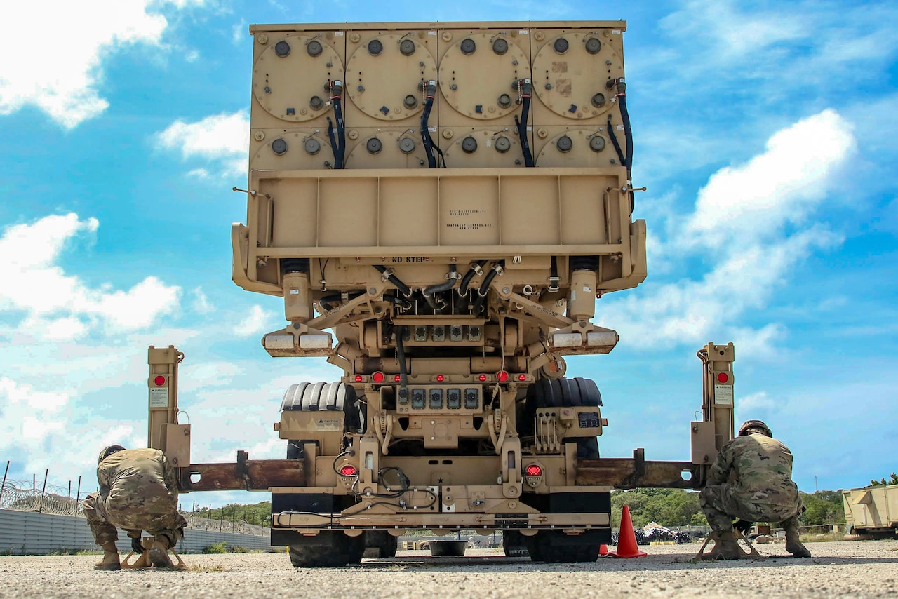 Two soldiers work on a large missile defense system.