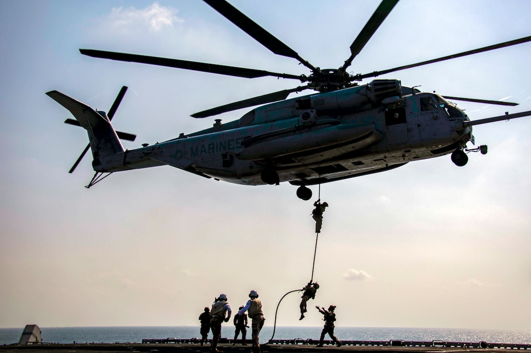 Marines climb down a rope hanging out of a helicopter onto the flight deck of a navy ship.