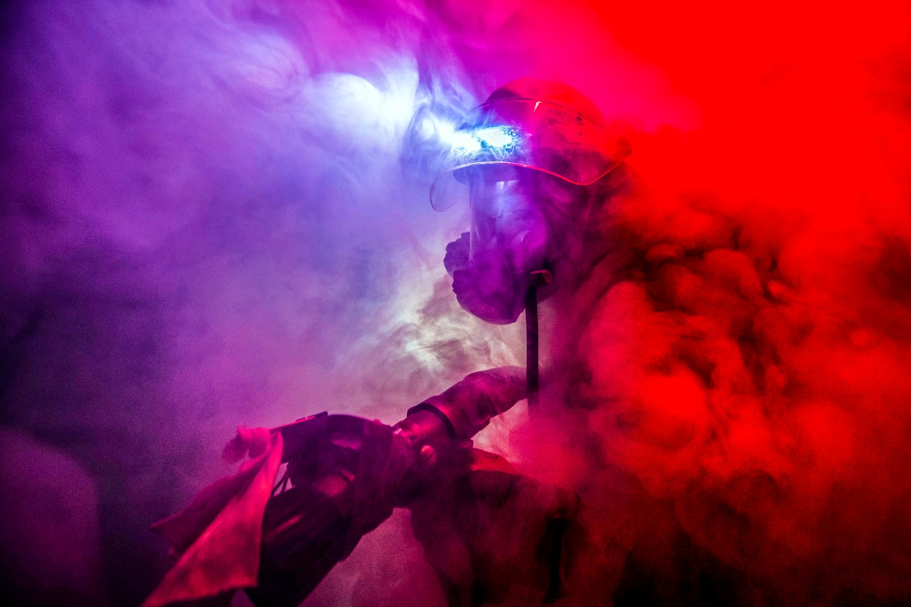A sailor walks through thick smoke in close quarters.