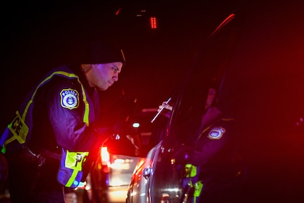 Shaun Turner, 628th Security Forces Squadron patrolman, checks a driver's insurance during a DUI checkpoint Feb. 3, 2019, at Joint Base Charleston, S.C.