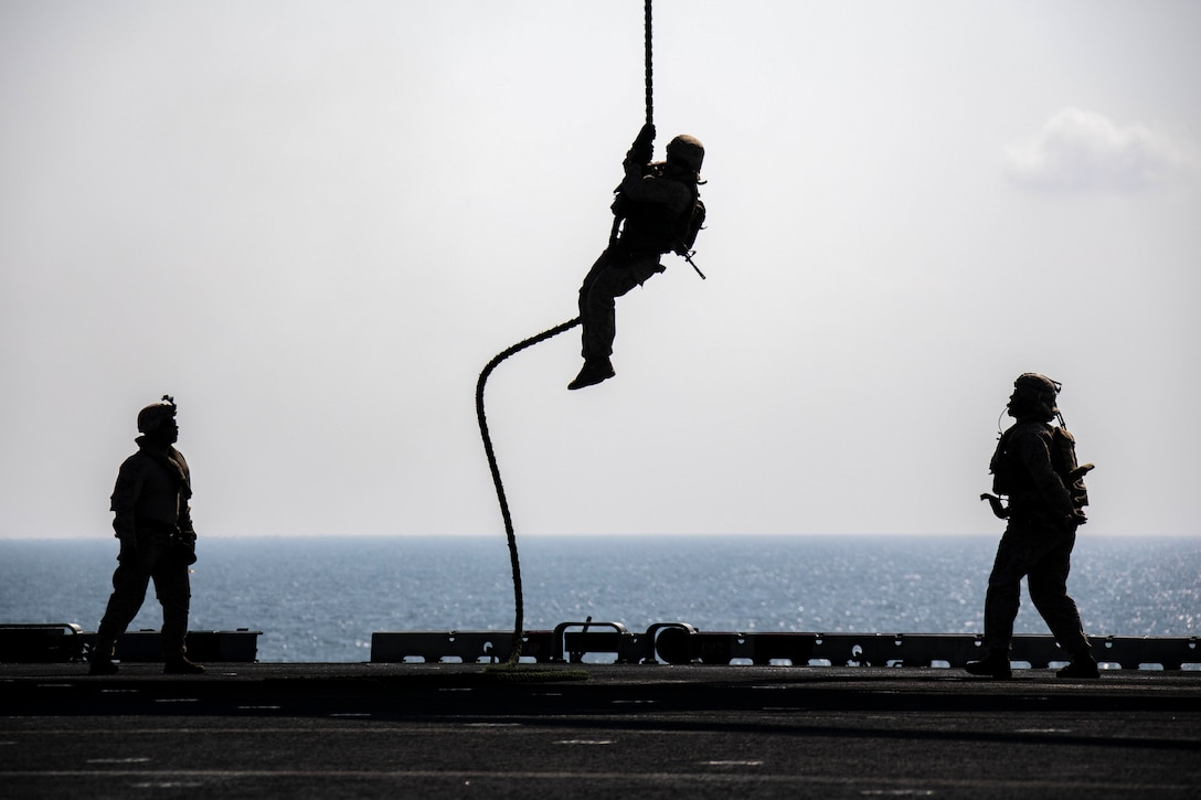 A Marine slides down a rope while two other Marines stand on either side.