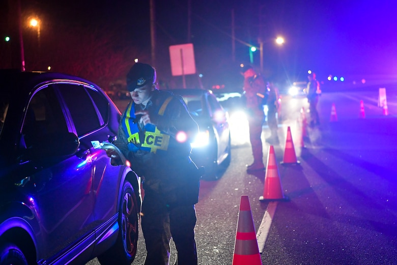 628th Security Forces Squadron patrolmen check drivers' insurance and registration during a DUI checkpoint Feb. 3, 2019, at Joint Base Charleston, S.C.