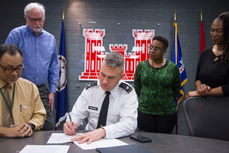 Norfolk District Commander, Col. Patrick Kinsman signs the Norfolk Harbor Navigation Improvements Design Agreement as District employees look on today at the District headquarters building.