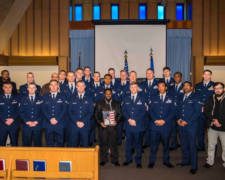 "Members of the ""Dirt Boyz"" of the 633rd Civil Engineer Squadron pose with a photograph of U.S. Air Force Tech. Sgt. Jason Kelley, 633rd CES NCO in charge of pavements and equipment, during Kelley's funeral service at Bethel Chapel at Joint Base Langley-Eustis, Virginia, Jan. 21, 2019. Dirt Boyz attended the funeral to show support for the family of the man they worked alongside throughout his cancer treatment and his career in the U.S. Air Force. (U.S. Air Force photo by Airman 1st Class Marcus M. Bullock)"
