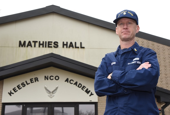 U.S. Coast Guard Boatswain's Mate 1st Class Paul McCann, U.S. Coast Guard Sector New Orleans Aids to Navigation Team Dulac executive petty officer, stands in front of the Mathies NCO Academy building at Keesler Air Force Base, Mississippi, Feb. 6, 2019. McCann is the first Coast Guardsman to attend the Academy at Keesler. Mathies NCOA is focused on developing enlisted leaders and delivering capabilities to combatant commanders and other sister services. (U.S. Air Force photo by Kemberly Groue)