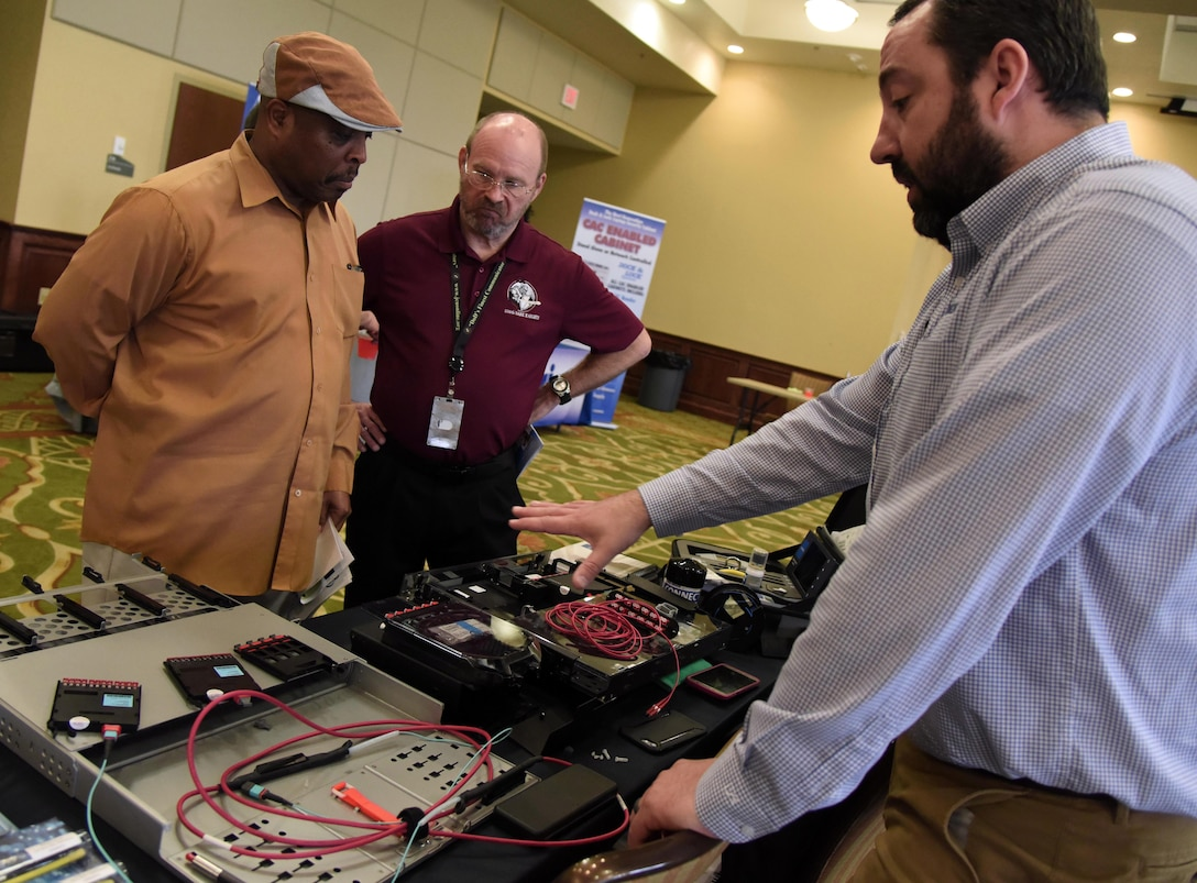 Derek Benson, Corning Optical Communications LLC sales engineer, provides an equipment brief to William Scott, 338th Training Squadron instructor supervisor, and Michael Clark, 338th TRS resource advisor, during the Annual Keesler Air Force Base Tech Expo inside the Bay Breeze Event Center at Keesler Air Force Base, Mississippi, Feb. 5, 2019. The expo was hosted by the 81st Communications Squadron and was free to all Defense Department, government and contractor personnel with base access. U.S. Air Force Maj. Jon Drummond, 81st CS commander, said events like this allows us to see the local vendors' newest technologies and find opportunities to branch that technology with Keesler's training mission. The event was held to introduce military members to the latest in technological advancements to bolster the Air Force's capabilities in national defense. (U.S. Air Force photo by Kemberly Groue)