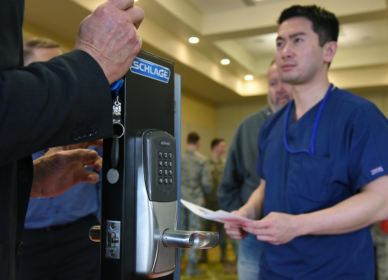 Johnny Truong, VA Hospital chiropractor, watches a demonstration on a common access card lock given by Terry Collins, Allegion government sales director, during the Annual Keesler Air Force Base Tech Expo inside the Bay Breeze Event Center at Keesler Air Force Base, Mississippi, Feb. 5, 2019. The expo was hosted by the 81st Communications Squadron and was free to all Defense Department, government and contractor personnel with base access. U.S. Air Force Maj. Jon Drummond, 81st CS commander, said events like this allows us to see the local vendors' newest technologies and find opportunities to branch that technology with Keesler's training mission. The event was held to introduce military members to the latest in technological advancements to bolster the Air Force's capabilities in national defense. (U.S. Air Force photo by Kemberly Groue)