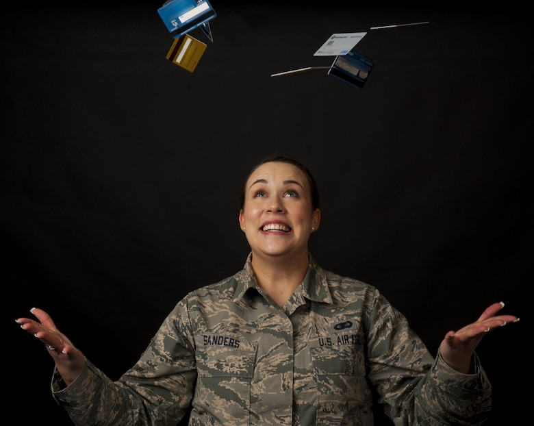 "In this photo illustration, Staff Sgt. Kya Sanders, 90th Security Support Squadron administration, tosses away credit cards, symbolizing the credit card debt she and her fellow Financial Peace University graduates eliminated and the credit card offers they turned down during the 12-week course. The FPU course hosted by the 90th Missile Wing chapel follows financial author and spokesman Dave Ramsey's ""Financial Peace Military"" curriculum, which is similar to the standard FPU course, but with an emphasis on military-specific financial topics. (U.S. Air Force photo illustration by Senior Airman Jason Wiese)"
