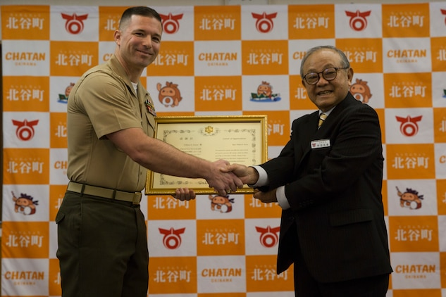 Maj. William Easter, left, a theatre security cooperation officer with III Marine Expeditionary Force, receives a letter of appreciation from Masaharu Noguni, the Mayor of Chatan, right, at the Chatan Town Office, Okinawa, Japan, Jan. 22, 2019.