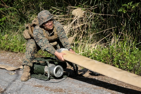 Pfc. Gilberto Loza-Machado pulls on a fuel hose to be attached to a meter on Jan. 28, 2019 at Central Training Area, Camp Hansen, Okinawa, Japan.