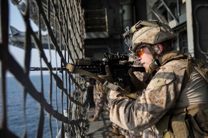 U.S. Marine Corps Lance Cpl. Kenneth Barrett, a machine gunner with the 22nd Marine Expeditionary Unit, sights in during a deck shoot as a part of Tactical Recovery of Aircraft and Personnel training aboard the USS Kearsarge. Marines with Alpha Company, 1st Battalion, 2nd Marine Regiment conducted TRAP training as preparation for entering combative areas and retrieving or destroying sensitive material as well as recovering personnel. Marines and Sailors with the 22nd MEU and Kearsarge Amphibious Ready Group are deployed to the 5th Fleet area of operations in support of naval operations to ensure maritime stability and security in the Central Region, connecting the Mediterranean and the Pacific through the western Indian Ocean and three strategic choke points.