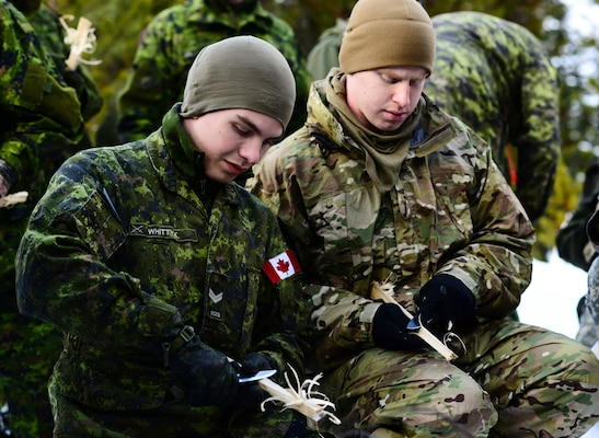 Oregon Army National Guard Staff Sgt. Eric Givens, right, with Delta Company, 2nd Battalion, 162nd Infantry Regiment, 41st Infantry Brigade Combat Team, and Canadian Army Reserve Cpl. Avery Whitty-Kirker, with Royal Westminster Regiment, 39th Canadian Brigade Group, use knives to feather kindling sticks as part of a fire making class taught by the 4th Canadian Rangers Patrol Group during Westie Avalanche Exercise, Jan. 26, 2019, at E.C. Manning Park, British Columbia, Canada.