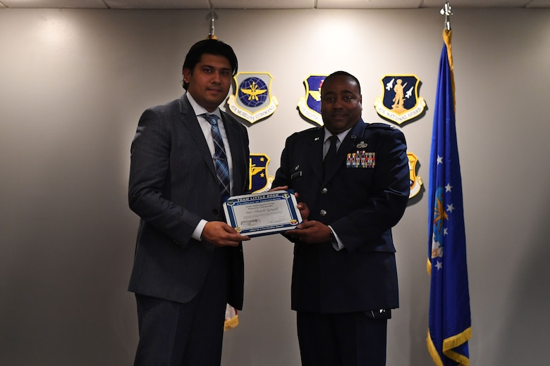 Two men stand and hold a certificate.