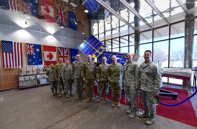 Gen. Jay Raymond (center), Air Force Space Command commander, and Chief Master Sgt. Roger Towberman (right of center), AFSPC command chief, stand with Col. Troy Endicott, 460th Space Wing commander, and other members of Team Buckley in the Space Based Infrared Systems Mission Control Station lobby during a tour of Buckley Air Force Base, Colorado, Feb. 1, 2019. (U.S. Air Force photo by Senior Airman Jazmin Smith)