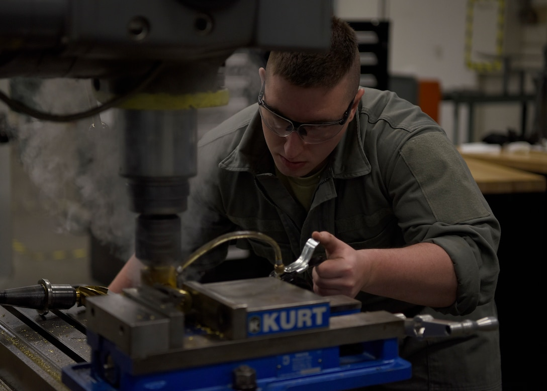 Airman 1st Class Taylor Frost, 56th Equipment Maintenance Squadron aircraft metals technology apprentice, shaves down an ammunition shell, Feb. 6, 2019 at Luke Air Force Base, Ariz.