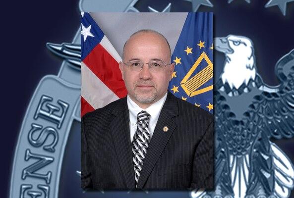 A portrait of Mike Scott over a DLA emblem background