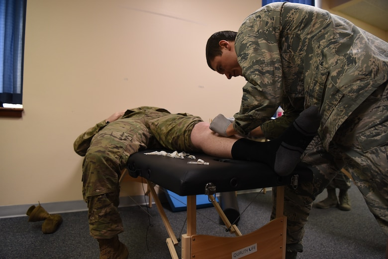 Captain Eric Walter, 90th Medical Operations Squadron physical therapy flight commander, performs dry needling on a 890th Missile Security Forces Squadron defender during a weekly squadron visit Feb. 4, 2019, at F.E. Warren Air Force Base, Wyo. The 90th MDOS PT team created a physical therapy program to provide better access to care, working around the unique schedules of defenders. (U.S. Air Force photo by Senior Airman Abbigayle Williams)