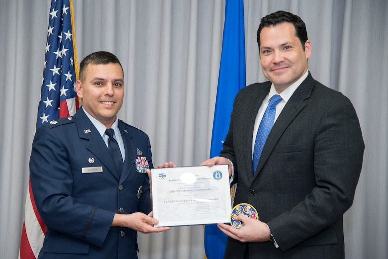 433rd Training Squadron Commander Lt. Col. Christopher Victoria presents the induction certificate to the squadron's new honorary commander, Bexar County Precinct 2 Commissioner Justin Rodriguez, during the Feb. 1 honorary commander induction ceremony held at Joint Base San Antonio-Randolph, Texas. (U.S. Air Force photo by Sean Worrell)