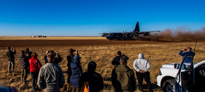 A group of people watching an aircraft land