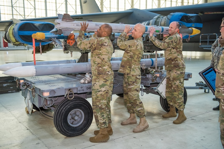 Brig. Gen. E. John Teichert, 412th Test Wing commander (right), and Chief Master Sgt. Roosevelt Jones, 412th TW command chief, help 412th Maintenance Squadron first sergeant, Master Sgt. Robert Forbes, load an AIM-9X Sidewinder short-range air-to-air missile on an F-16 Fighting Falcon Feb. 6.  