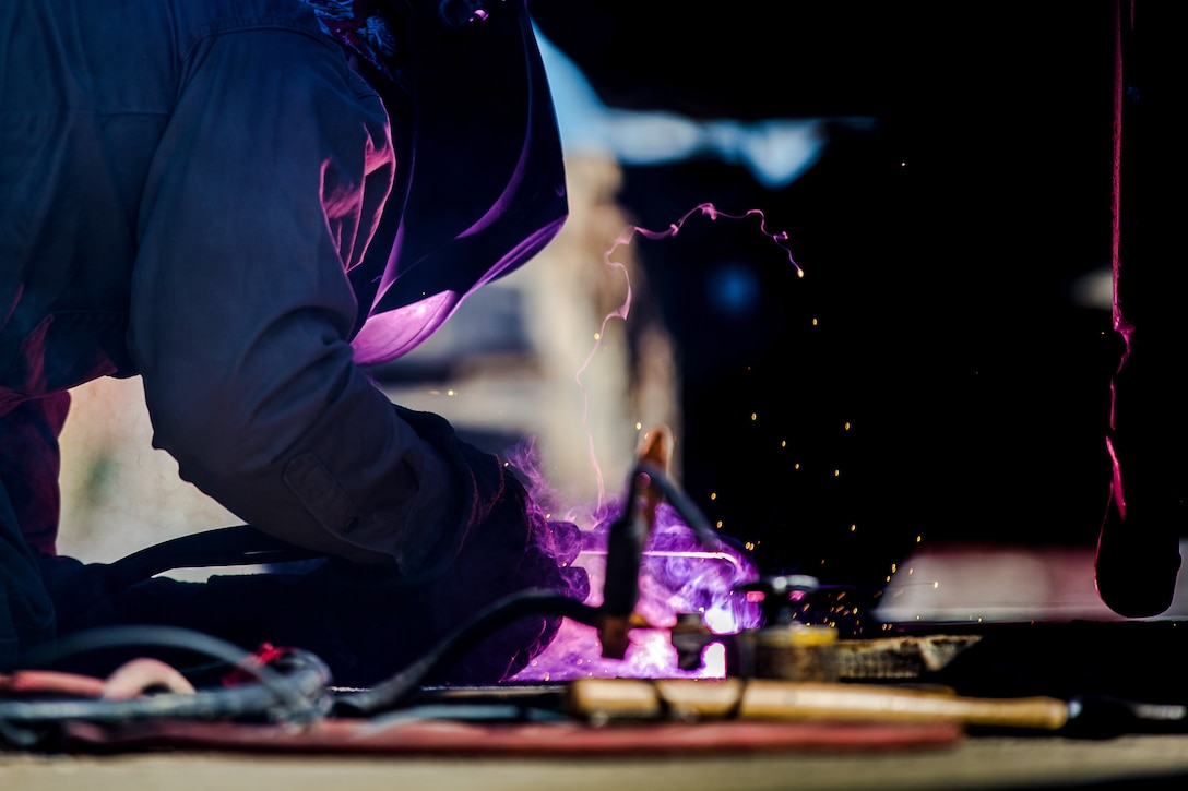 Sparks and purple smoke fly as a welder works on a steel plate.
