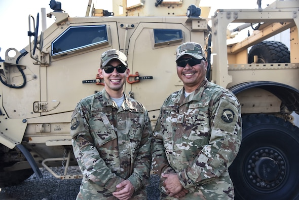 U.S. Air Force Senior Airman Anthony Castro and Master Sgt. Jonathan Herrera, assigned to the 380th Expeditionary Logistics Readiness Squadron Petroleum, Oil and Lubricants flight, pose for a photo at Al Dhafra Air Base, United Arab Emirates, Dec. 13, 2018. Castro is on his first deployment, while Herrera is potentially on his last deployment, as he's nearing retirement. (U.S. Air Force photo by Senior Airman Mya M. Crosby)